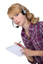 A businesswoman with a headset on taking notes Stock Photography