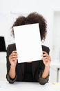 Businesswoman hiding behind a blank sheet of paper with bushy afro hairstyle covering her face as she sits at her desk Royalty Free Stock Images