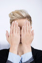 Businesswoman hiding face with hands in office closeup of young Stock Image