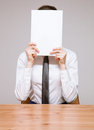 Businesswoman hiding her face behind documents gray background Stock Image