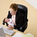 Businesswoman holding baby at desk Royalty Free Stock Images