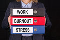 Businesswoman holding black red and blue lever arch files boldly marked work burnout and stress in black upper case letters Royalty Free Stock Images