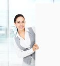 Businesswoman holding a blank white card board signboard showing an empty bill young business woman happy smile in modern Royalty Free Stock Photo