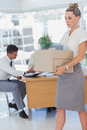 Businesswoman holding a box and his colleagues in the bottom office Royalty Free Stock Image