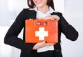 Businesswoman holding first aid box Royalty Free Stock Photo