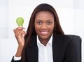 Businesswoman holding green electric bulb in office Royalty Free Stock Photo