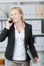 Businesswoman holding laptop while using mobile phone happy young in office Royalty Free Stock Images