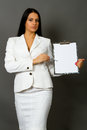 Businesswoman holding a pen requesting signature on document isolated on gray background Stock Photos