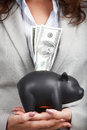 Businesswoman holding the piggy bank and dollar bills in her hands Stock Photography