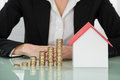 Businesswoman With House Model And Stacked Coins On Desk Royalty Free Stock Photo
