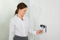 Businesswoman inserting keycard in security system young smiling while door Stock Photos