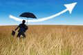 Businesswoman jumping to blue sky in grassland with umbrella Stock Photography