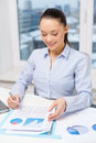 Businesswoman with laptop and charts in office business technology internet concept smiling Royalty Free Stock Photo