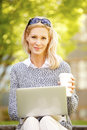 Businesswoman with laptop coffee break outdoor a happy mature beautiful professional sits at an outdoor in the park and smiling Stock Images