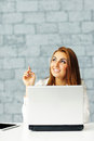 Businesswoman with laptop pointing up at copyspace young happy Royalty Free Stock Photo