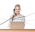 Businesswoman with laptop tied with phone cable Stock Image
