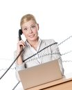 Businesswoman with laptop tied with phone wire Stock Photo