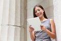 Businesswoman lawyer using digital tablet app pc computer outside in front of courthouse smiling happy looking at camera beautiful Royalty Free Stock Images