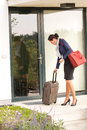 Businesswoman leaving house traveling carrying baggage hurried