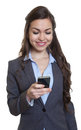 Businesswoman with long brown hair writing message with phone Royalty Free Stock Photo
