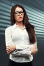 Businesswoman looking at camera wearing glasses in front of a striped background the Royalty Free Stock Photos
