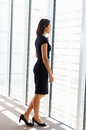 Businesswoman looking out of window office Stock Image