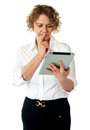 Businesswoman looking at tablet and thinking deep Stock Images