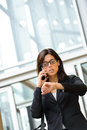 Businesswoman looking time in watch stressed business woman leaving corporate city building a hurry her and talking on cellphone Royalty Free Stock Images
