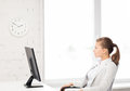 Businesswoman looking at wall clock in office picture of Royalty Free Stock Photography