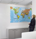 Businesswoman looking at world map in office rear view of a the Stock Images