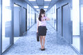 Businesswoman looks hurried in the office corridor