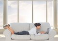 Businesswoman lying on couch using laptop composite image of in bright d room with windows Royalty Free Stock Photo
