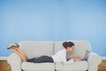 Businesswoman lying on couch using laptop composite image of in front of blue wall Royalty Free Stock Photo
