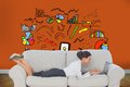 Businesswoman lying on couch using laptop composite image of in front of orange wall with economic illustrations Stock Photos