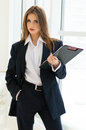 Businesswoman in man s suit shirt writing with pen at her office fashion styled business woman holding and looking camera Royalty Free Stock Images
