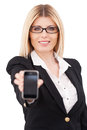 Businesswoman with mobile phone confident mature showing her and smiling while standing isolated on white Royalty Free Stock Photo