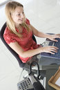 Businesswoman in office typing on computer Stock Photos