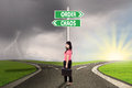 Businesswoman with order and chaos direction standing on the road signpost of Royalty Free Stock Images
