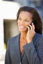 Businesswoman outside office on mobile phone smiling Stock Image