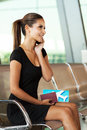 Businesswoman phone airport smiling talking on cell while waiting for her flight Stock Photo