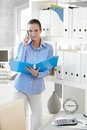 Businesswoman on phone call holding folder Royalty Free Stock Photo
