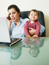 Businesswoman on the phone, holding daughter Royalty Free Stock Image