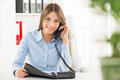 Businesswoman phoning young business woman in office sitting at an office desk with one hand holding the phone and in another Royalty Free Stock Photo