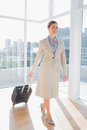 Businesswoman pulling her suitcase in large bright office Stock Photography