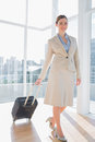 Businesswoman pulling her suitcase and smiling at camera in birhgt office Royalty Free Stock Photo