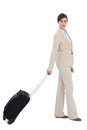 Businesswoman pulling suitcase against white background Stock Photos