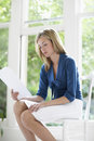 Businesswoman reading document at home beautiful young on chair Royalty Free Stock Image