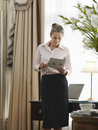 Businesswoman reading document in home office middle aged Stock Photo