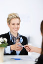 Businesswoman receiving cardkey from receptionist happy young at reception Stock Photo