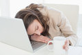 Businesswoman resting head on laptop keyboard young in a bright office Royalty Free Stock Image